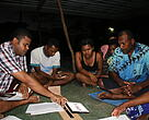 (Left) WWF-Pacific Coastal Fisheries officer Laitia Tamata discussing fish maturity sizes & species with Tavua villagers for better conservation methods.