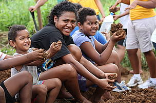 Volunteer Kalisiana Marama having fun mulching soil with children of Villa Maria Settlement